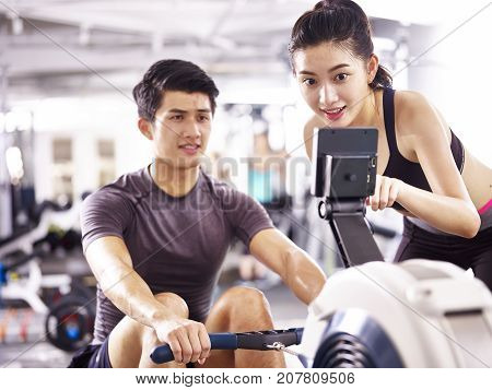 young asian man and woman working out in fitness center using rowing machine.