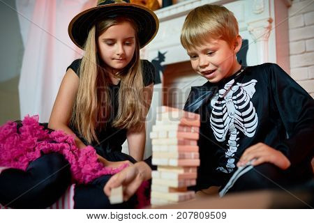Handsome little boy and his pretty elder sister wearing Halloween costumes sitting on floor of living room and playing board game with enthusiasm