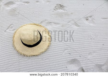 woven hat on the white sand beach.