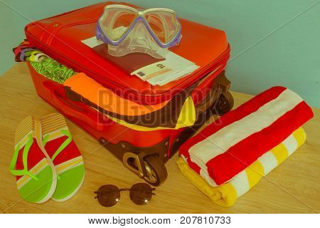 Suitcase with things for spending summer vacation things prepared for travel. Red suitcase with different things - Retro color