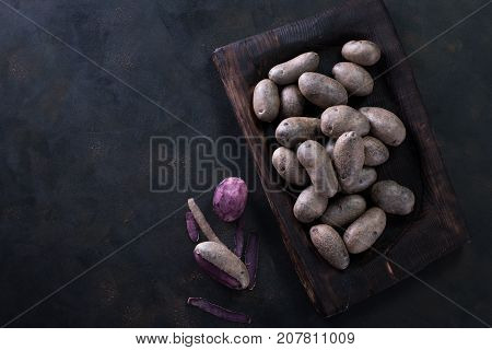 Raw Potato Food . Fresh Blue Potatoes On Dark Background. Free Place For Text.