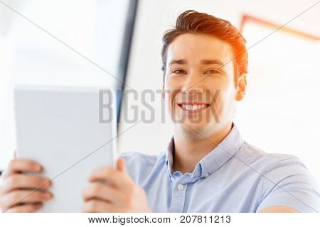 Young handsome businessman using his touchpad sitting in office