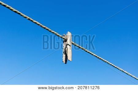 Old wooden clothespin on the rope against the blue sky