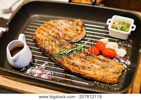 Grilled pork tomahawk (pork chop) with tamarind sauce black pepper sauce tomato garlic and salt serve on black hot pan.