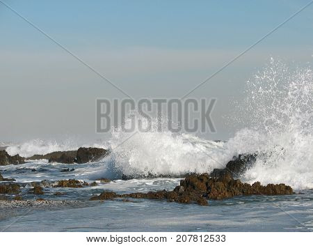 WINTER SEASCAPE, WITH HUGE WAVES SMASHING AGAINST SOME ROCKS AND SHOOTING UP INTO THE AIR