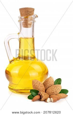 Bottle of almond oil and almonds with leaves isolated on white background.