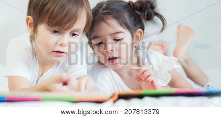 Brothers and sister read a bedtime story togather on the bed in bedroom kid child family study education and home work concept