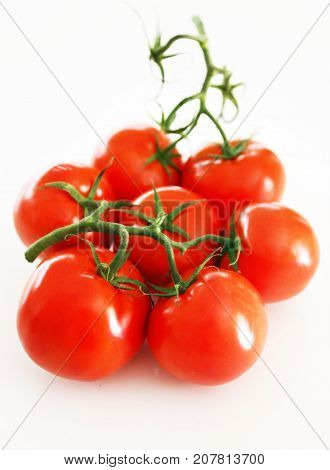 still life of fresh red tomatoes with green stalk isolated on white background