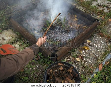 Woman getting rid of domestic waste in a garden bonfire, outdoor shot