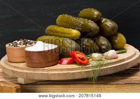 a set of cucumbers next to spices pepper and salt on a wooden table