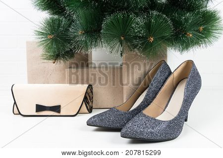 shiny pair of shoes and a small bag stand under a Christmas tree