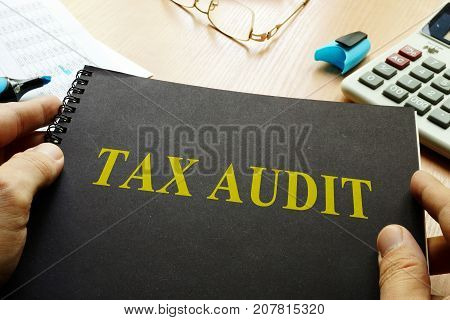 Book about tax audit and calculator on a desk.
