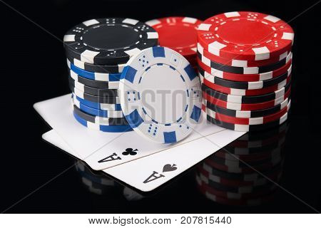 Two aces on a black background with a big bet of game money