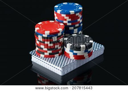 high bet of red chips on a deck of game cards on a black table with reflection