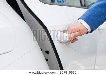 opening a door a white car a man in a blue business suit