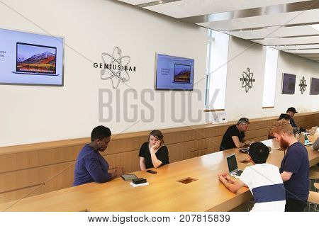 New York September 25 2017: Apple customers are receiving help at the Genius bar section of an Apple store.