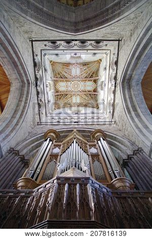 St Davids, Pembrokeshire, UK: October 27, 2012: Dramatic view of the ceiling and church organ in St Davids Cathedral. The cathedral was founded by Saint David of Menevia who died in 589.