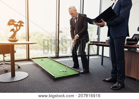 A respectable middle-aged man is playing golf in the office. A subordinate came to his office with a report