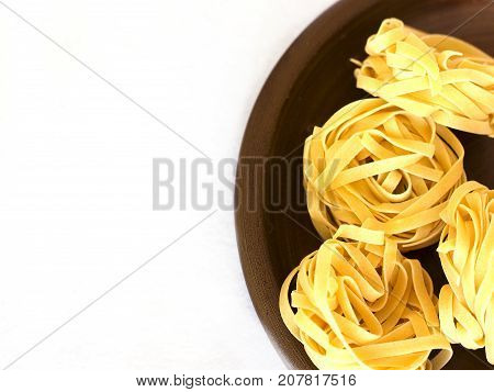 Uncooked Tagliatelle On A Ceramic Plate. Isolated