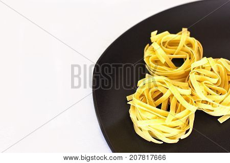Uncooked raw tagliatelle on ceramic plate. Isolated