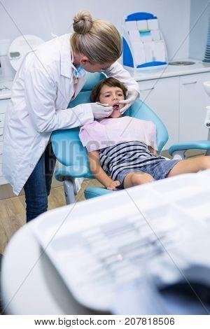 Female doctor examining boy at dental clinic