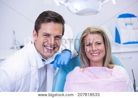 Portrait of woman sitting on chair by dentist at clinic