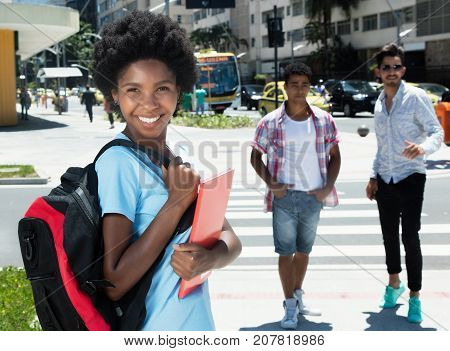 Happy african american female student in the city in the summer