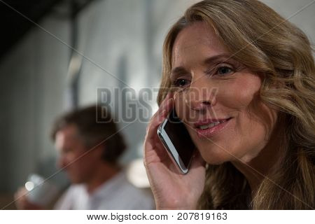 Close-up of woman talking on mobile phone in restaurant