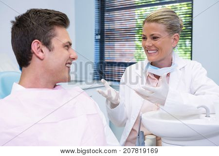 Happy patient discussing with dentist at dental clinic