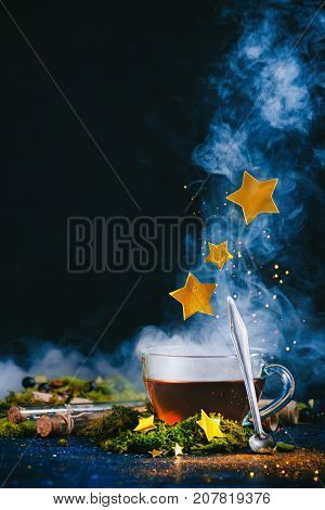 A Cup Of Tea With Dense Steam, An Antique Spoon, Golden Stars And Magical Pixie Dust On A Dark Backg