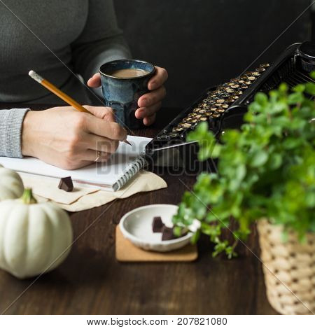 The writer's place with a vintage black typewriter. A woman makes notes in a notebook and holds a glass of coffee. Autumn decoration with small white pumpkin. Life style. Retro