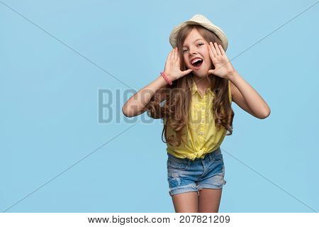 Charming little model in straw hat holding hands near mouth calling loud on blue background.