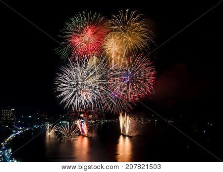 Colourful Fireworks over the sea beach with dark black sky background and city view