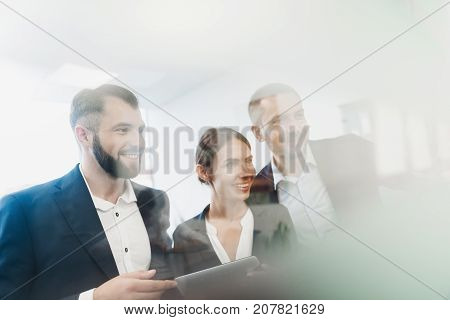 Two men and a woman in strict business suits are posing and smiling. They look at the glass wall hung with paper stickers. One of the men in the hands of a tablet