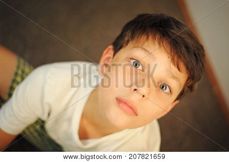 Boy in shorts and a white T-shirt sitting and resting. Looking directly at the camera. He has serious brooding look