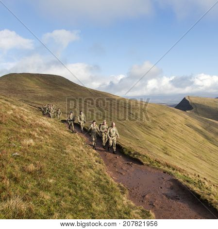 Brecon, Wales, UK: January 08, 2015: A group of soldiers on a training exercise on the Brecon Beacons with Pen y Fan behind. They are wearing fatigues and are walking towards the camera.