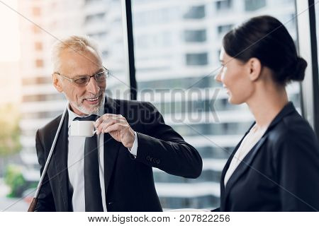 The old man is posing against the background of a large panoramic window. His secretary approached him and brought him coffee. He has a golf club behind him