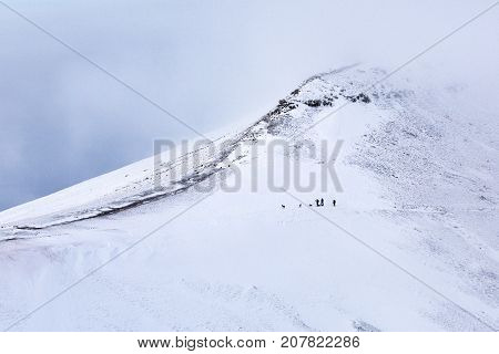 Extreme hiking on the snow covered mountain of Pen y Fan in the Brecon Beacons National Park, with poor visibility and dangerous climbing conditions. A group of unrecognizable people walk the on the ridge.