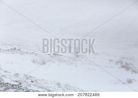 Snow covered mountain landscape of Pen y Fan mountain in the Brecon Beacons, Wales, UK with poor visibility and dangerous climbing conditions, two unrecognizable people are walking down the mountain path