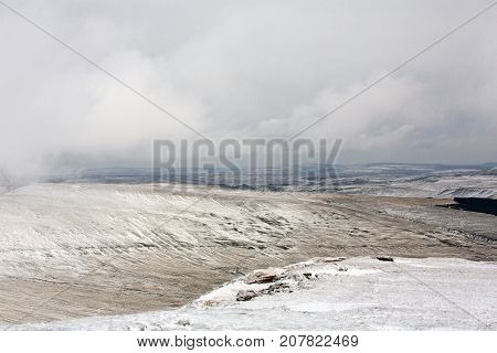 Landscape of Brecon Beacons from Pen y Fan with snow and icy conditions