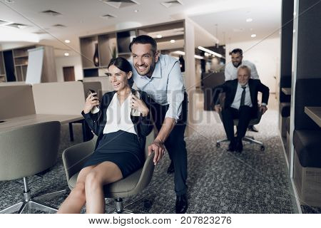 Office workers have fun in the office. A man is rolling a woman in an office chair. Behind them, another man rolls on the boss's chair. They arranged races on office chairs. They are having fun