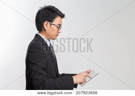 Young asian handsome businessman using his tablet on white backgrond.