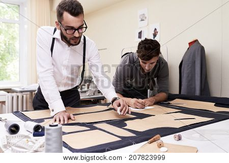 Portrait of two modern tailors working in atelier studio, making patterns for clothes and sketching at table with different tools