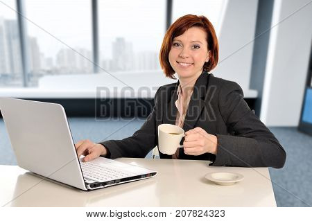 young happy business woman with red hair at work smiling on laptop computer desk and drinking coffee working satisfied at modern office workplace room in job and professional career success