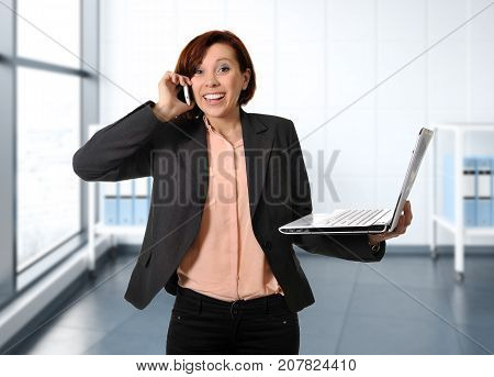 young happy business woman with red hair at work smiling with laptop computer talking busy on mobile phone working satisfied at modern office in job and professional career success