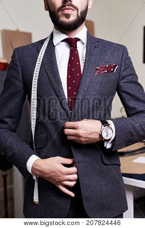 Mid section portrait of handsome bearded gentleman wearing fashionable suit and jacket posing in atelier studio