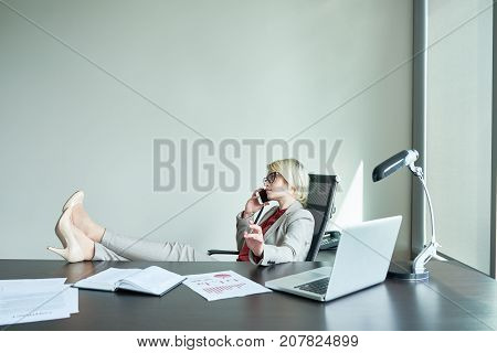 Portrait of successful female boss sitting at big desk in modern office speaking by phone with feet on table