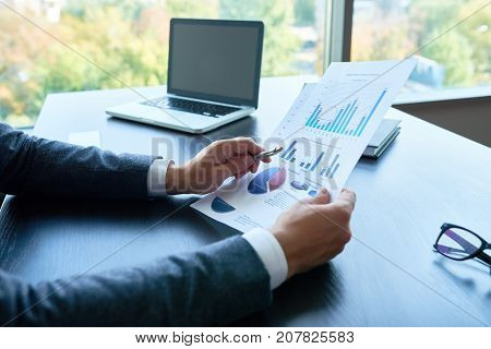 Closeup of unrecognizable business person  pointing to statistics graph analyzing marketing data in modern office, copy space