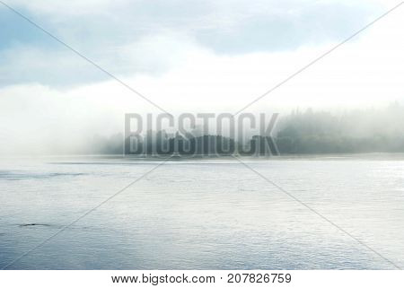 A view of a calm wide river covered with a morning mist. Slightly visible opposite shore.