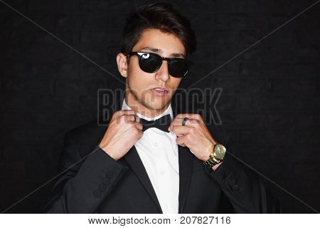 Handsome brunette man wearing black suit sunglasses with black frames golden watch adjusting bow tie.